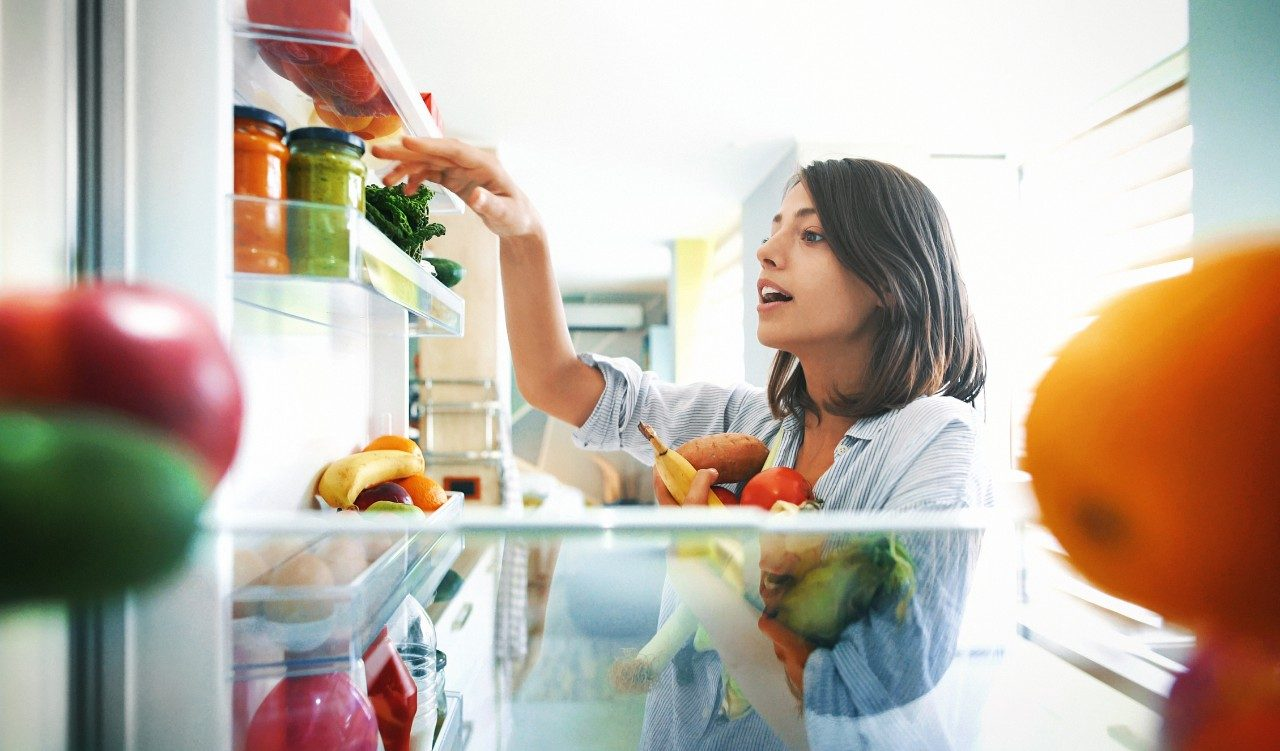 Closeup of a cheerful young couple picking some fruit and veggies from the fridge to make some healthy breakfast on Sunday morning. Shot from inside the working fridge.