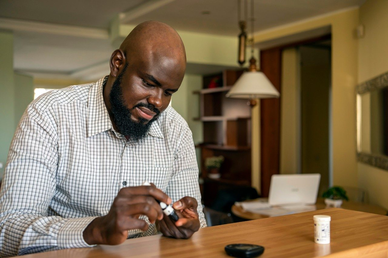 A modern African businessman is sitting at the desk at the home office and taking blood from his finger due to diabetes. The daily life of a man of African-American ethnicity person with a chronic illness who is using glucose tester.