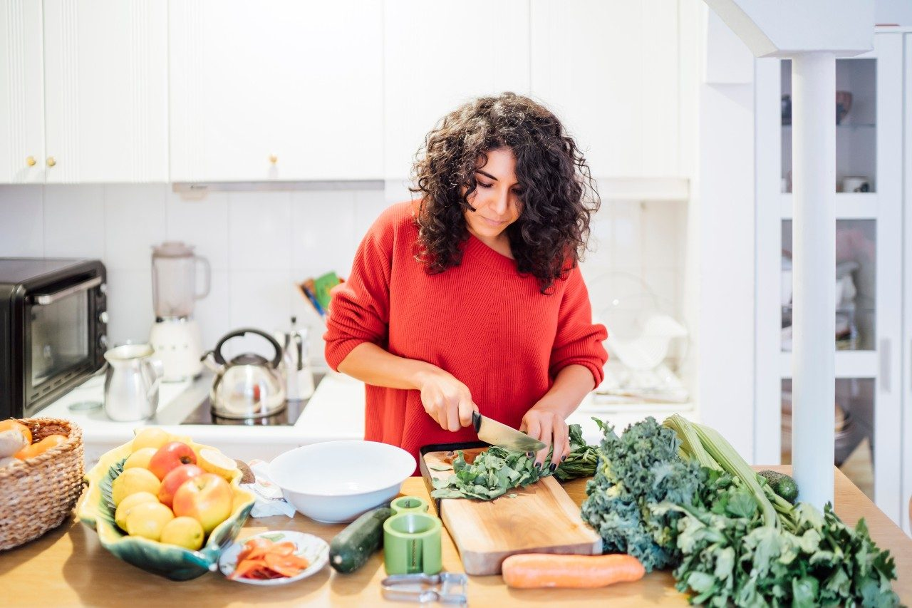 Brunette woman making a healthy green salad.