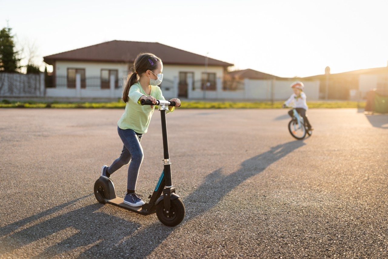 Child with protective face mask riding on scooter during corona virus pandemic