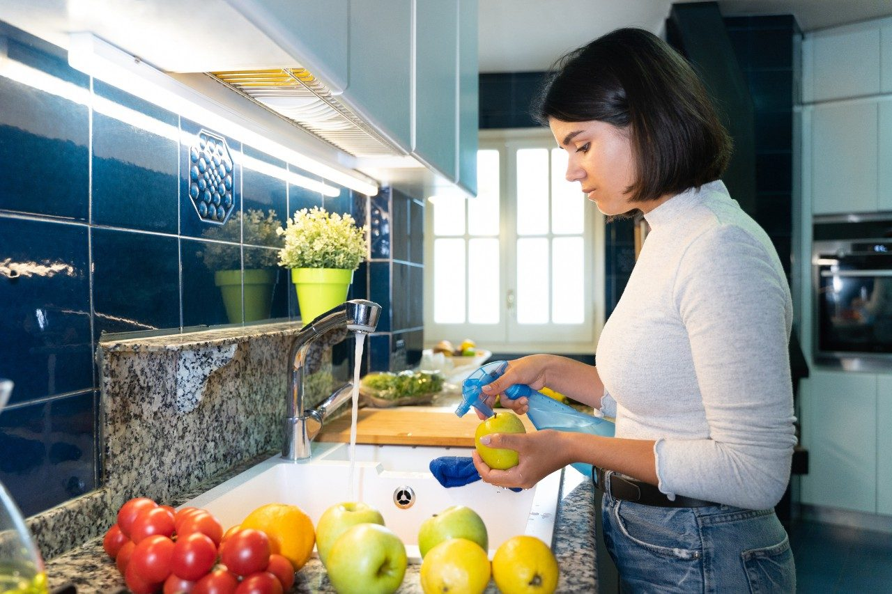 Woman disinfecting groceries in her kitchen, to avoid COVID-19. She is washing all the food after shopping to prevent illness.