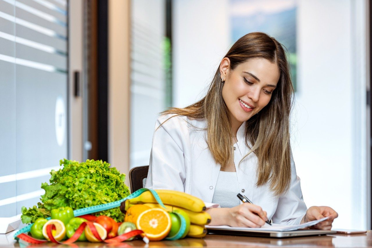 Smiling nutritionist in her office, she is showing healthy vegetables and fruits.