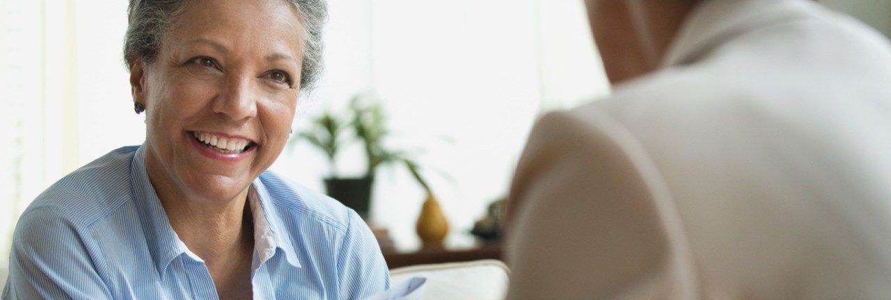 穿蓝色上衣的老年女人正在对某人微笑。