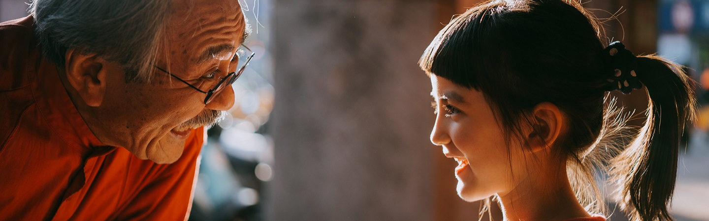 Profile view of cute young mixed race girl smiling at her Japanese grandfather with sunlight on street