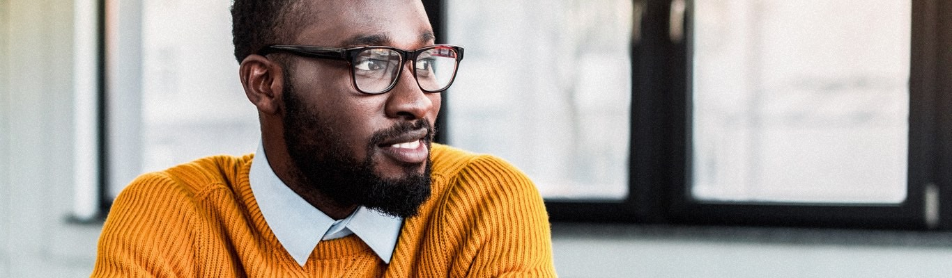 Man with beard in orange sweater and glasses.